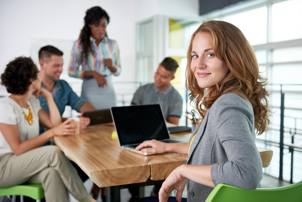 Image of a succesful casual business woman using laptop during meeting.jpeg