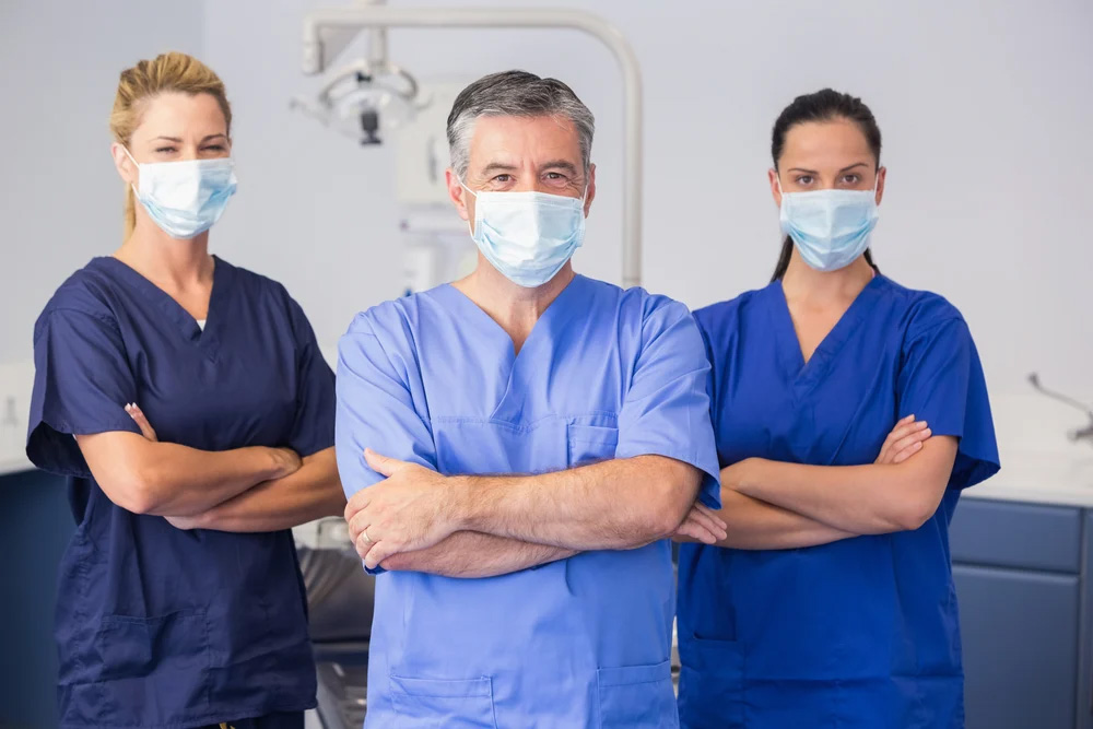 Three healthcare professionals standing with their arms crossed wearing masks